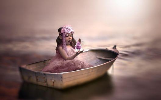 Обои Милая, темноволосая девочка, сидящая в лодке, приоткрыв от удивления рот рассматривает куклу-фею с белыми крылышками за спиной, находящуюся у нее на ладошке