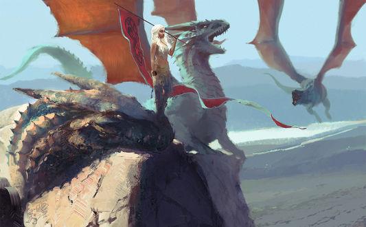 Обои Дайенерис Таргариен / Dayeneris Targaryen из сериала Игра престолов / Game of Thrones стоит на голове одного из трех драконов, держа в руках флаг