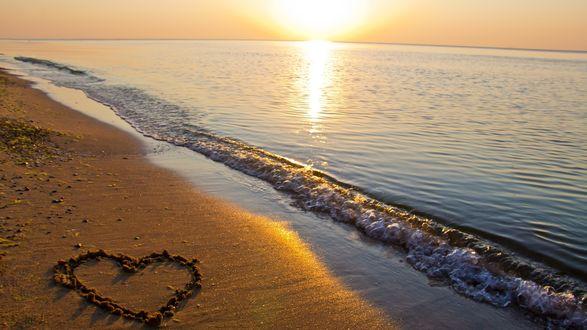 Обои Морская волна накатывается на рисунок на песке, в лучах восходящего солнца