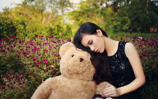Обои Девушка - азиатка сидит в цветах с плюшевым медведем