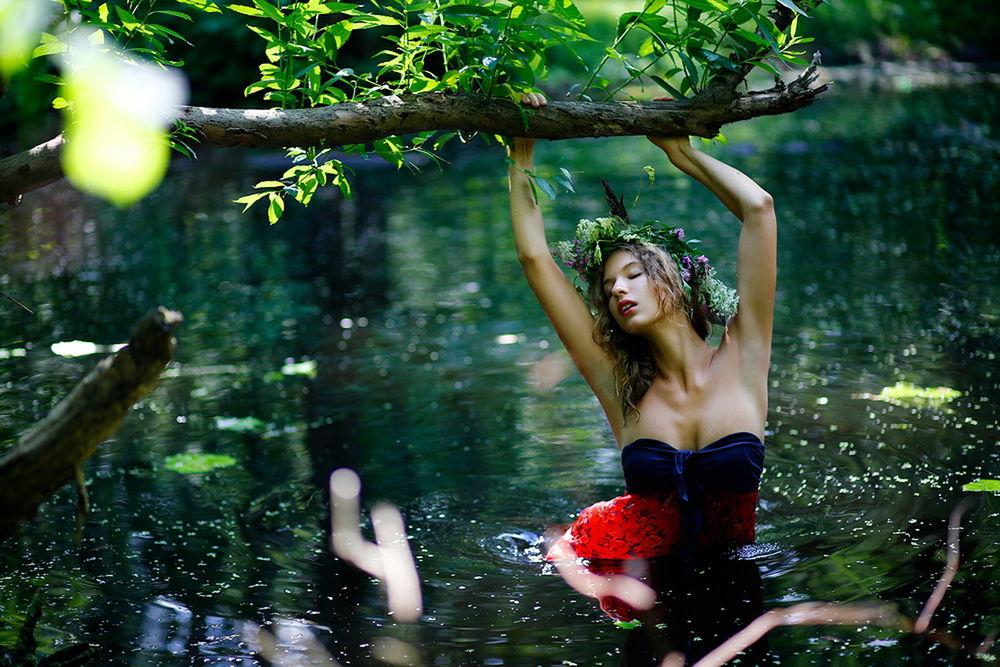 Обои для рабочего стола Темноволосая девушка с венком из полевых цветов на голове, с закрытыми глазами, стоящая в воде лесного ручью по пояс, держащаяся за ствол дерева двумя руками, автор Екатерина Постонен