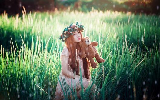 Обои Азиатка с игрушечным мишкой сидит в поле