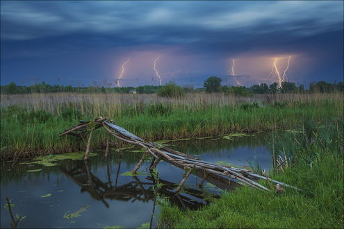 Обои Небольшой водоем с ветхим, деревянным мостиком на фоне грозового, темного неба и разрядов молнии