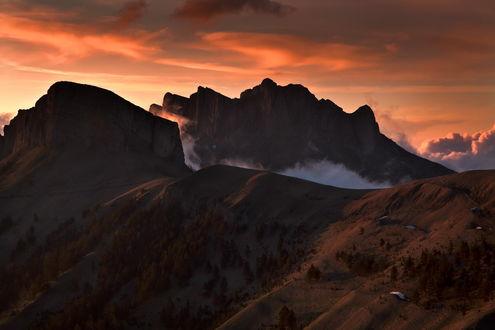 Обои Красивый горный ландшафт на фоне небосклона, покрытого разноцветными облаками