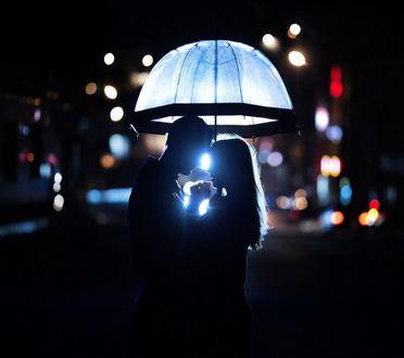 Обои Влюбленные юноша и девушка, стоящие под зонтом на фоне бликов ночного города