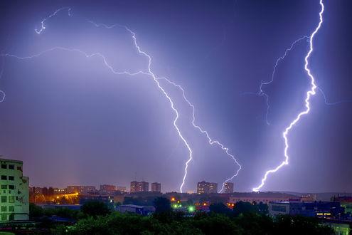 Обои Сверкающие разряды молнии в ночном небе над городской окраиной