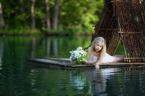 Обои Милая светловолосая девочка, лежащая на деревянном плоту с шалашом на водной глади озера, держащая в руке букет сирени