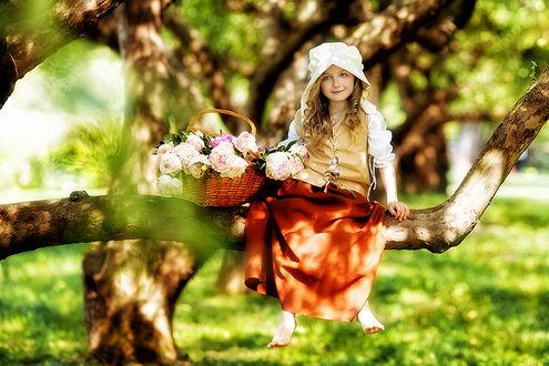 Обои Милая, босоногая девочка, сидящая на изогнутом стволе дерева рядом с плетеной корзинкой с цветами, освещенной солнечными лучами