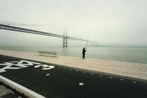 Обои Мужчина с удочкой в руке, стоящий на каменной набережной реки на фоне моста, уходящего в туманную мглу