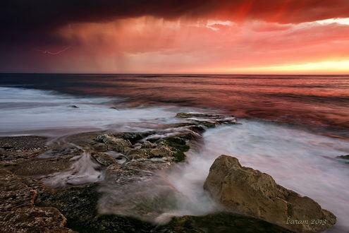 Обои Каменистое морское побережье на фоне грозовых туч на небе и сверкающей молнии
