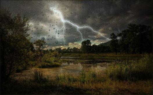 Обои Капли воды на стекле сквозь которое виднеется грозовое небо с черными тучами, вспышками молний над небольшим водоемом, заросшим травой, покрытым тиной