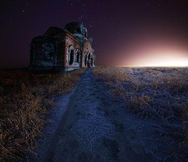 Обои Старая, заброшенная, кирпичная церковь, стоящая в поле, покрытом тонким слоем инея с проходящей мимо нее дорогой на фоне звездного, ночного неба
