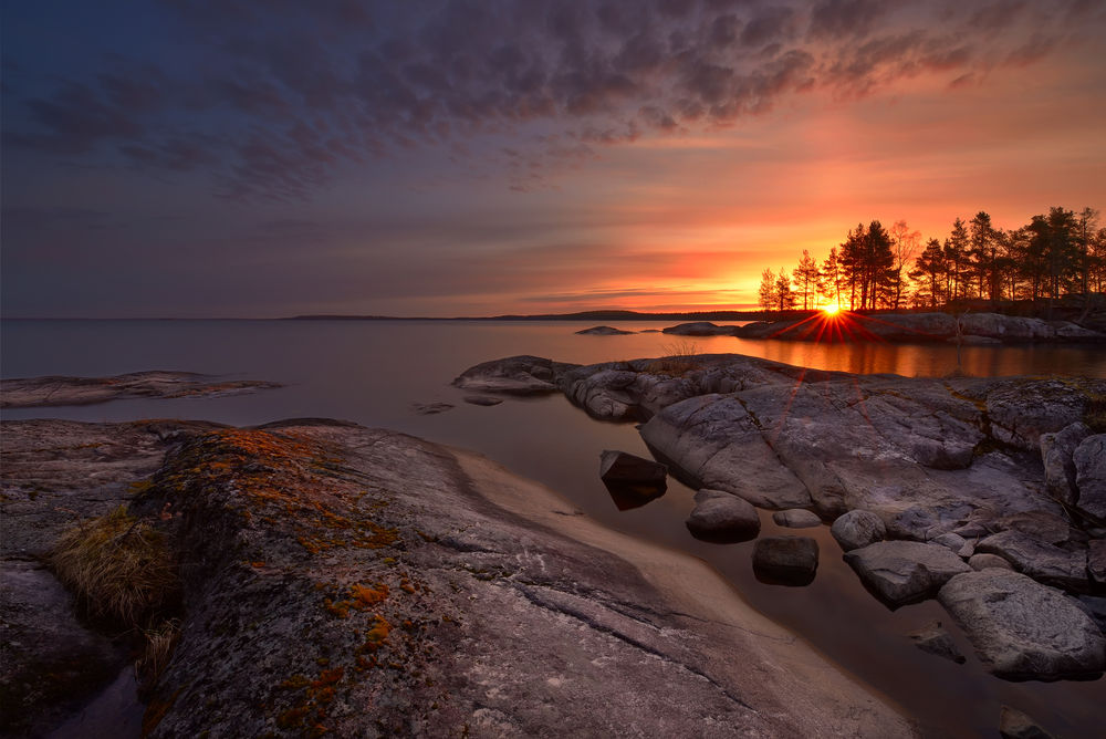 Обои для рабочего стола Каменистый берег моря на фоне багряного заката солнца