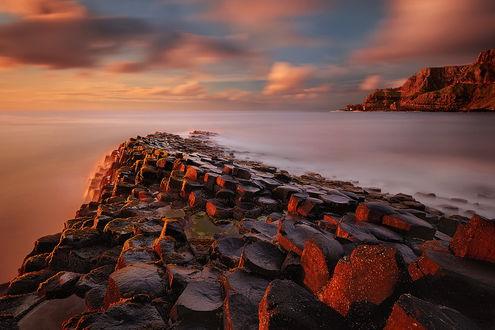 Обои Каменная гряда, уходящая в море, освещенная лучами закатного солнца на вечернем небосклоне с разноцветными облаками