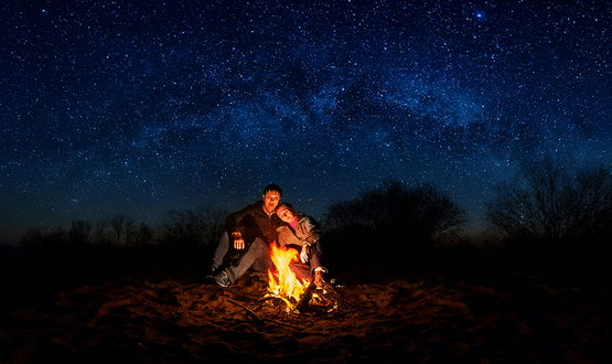 Обои Парень с девушкой, сидящие тесно прижавшись друг к другу у горящего костра на фоне звездного, ночного неба и Млечного пути