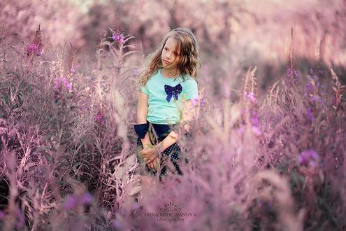 Обои Милая девочка, стоящая среди высоких кустов с фиолетовыми цветами на размытом фоне, автор Ирина Митрофанова