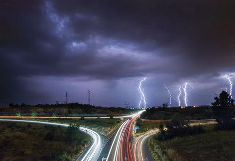 Обои Развилка скоростных, асфальтовых дорог со светящимися полосами от фар мчащихся на большой скорости автомобилей на фоне грозового, вечернего небосклона со сверкающими молниями