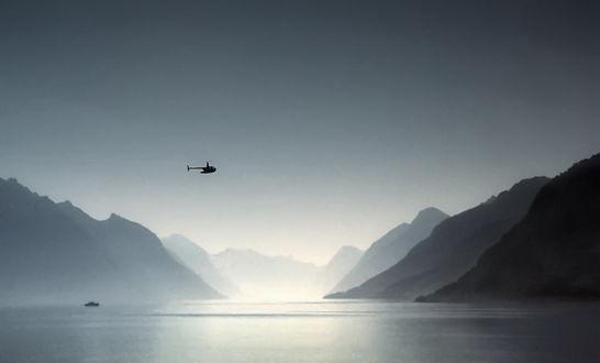 Обои Вертолет, пролетающий над горным озером с плывущим по его воде небольшим катером