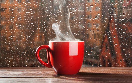 Обои Красная кружка с горячим чаем стоит на подоконнике, за окном идет дождь, оставляя на стекле капли