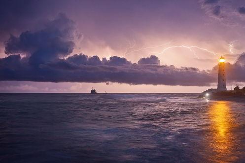 Обои Светящийся маяк, стоящий на морском побережье на фоне сверкающих молний на грозовом небосводе, плывущих рыбацких судов на линии горизонта