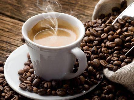 Обои Чашка кофе стоит рядом с мешком, из которого высыпались зерна кофе