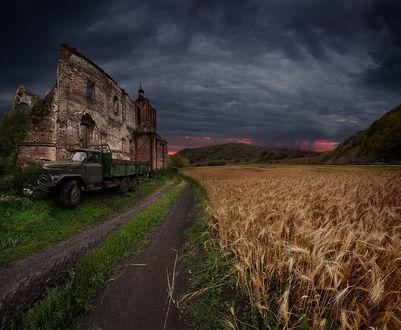 Обои Грузовой автомобиль, стоящий на обочине дороги у разрушенной кирпичной стены здания с проходящим по другую сторону дороги полем с поспевшей пшеницей на фоне темного, грозового неба