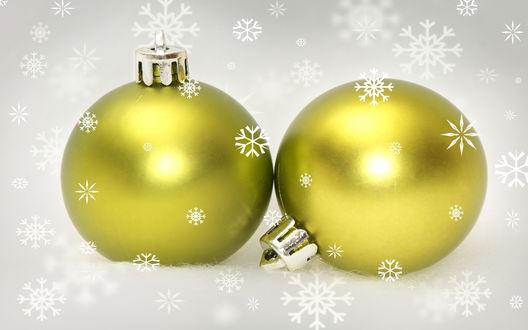 Обои Два золотых шара на белом фоне под падающими снежинками