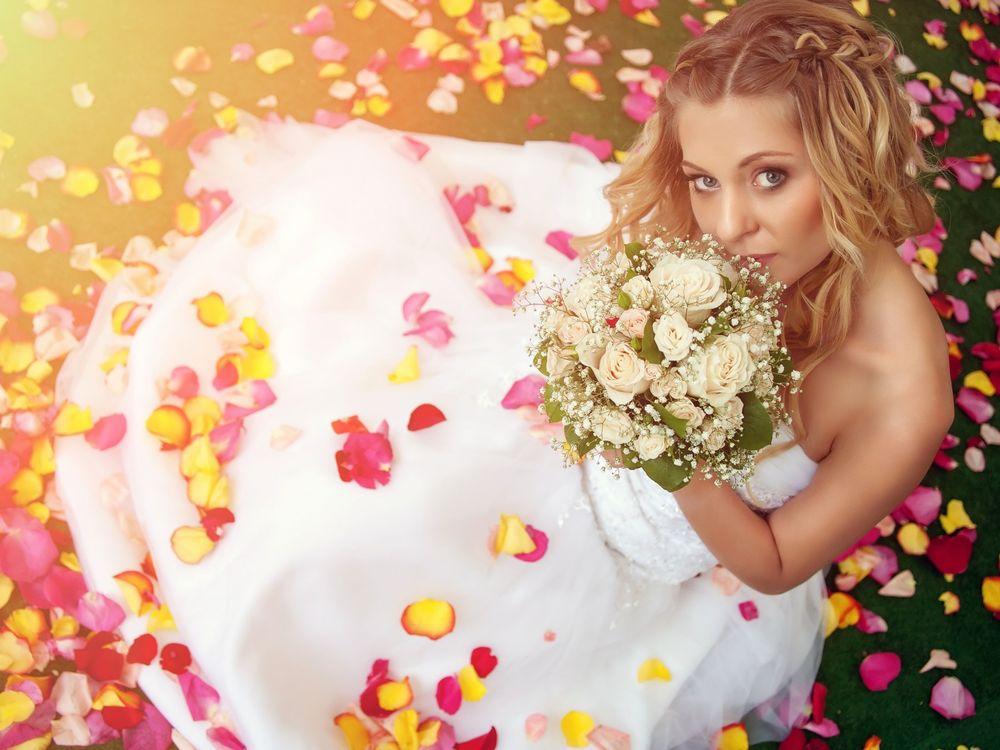 Обои для рабочего стола Девушка в свадебном платье с букетом в руках сидит, усыпанная лепестками роз