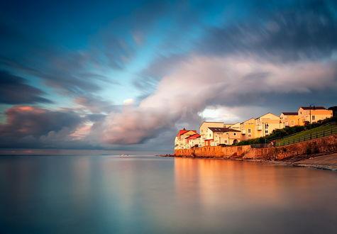 Обои Каменные дома, стоящие на морском побережье, освещенные солнечными лучами на фоне небосклона с разноцветными тучами
