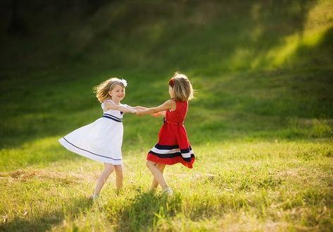 Обои Две улыбающиеся девочки, взявшись за руки кружатся на зеленой лужайке