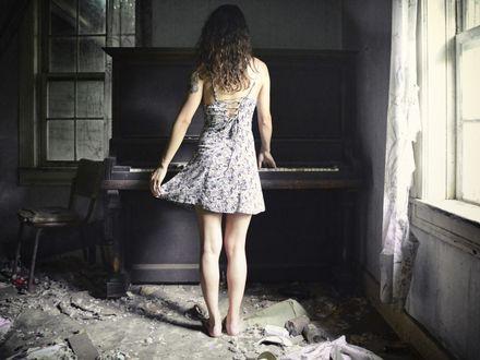 Обои Девушка в разрушенной комнате стоит спиной к камере возле фортепиано, касаясь руками его клавиш