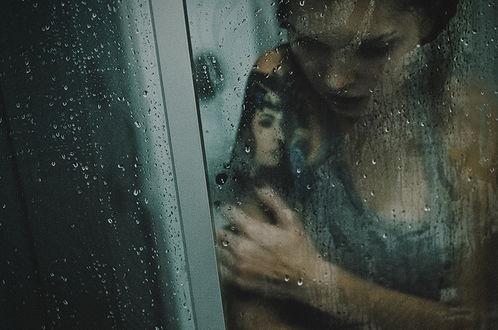Обои Темноволосая девушка с татуировкой женского лика на предплечье, стоящая за стеклом с каплями воды