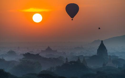 Обои Воздушные шары, парящие в воздухе над восточным городом с храмами, утопающими в зелени деревьев, покрытые легкой, туманной дымкой на фоне заката