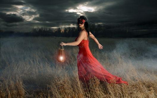 Обои Девушка с маской на лице и в красном платье стоит в поле с фонарем в руках