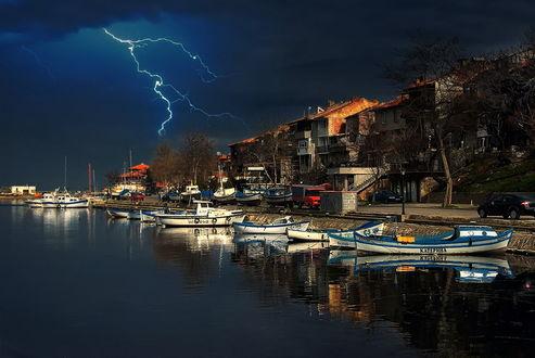 Обои Разряды молний на вечернем небосклоне над городской, речной набережной со стоящими у ее причала лодками и небольшими катерами