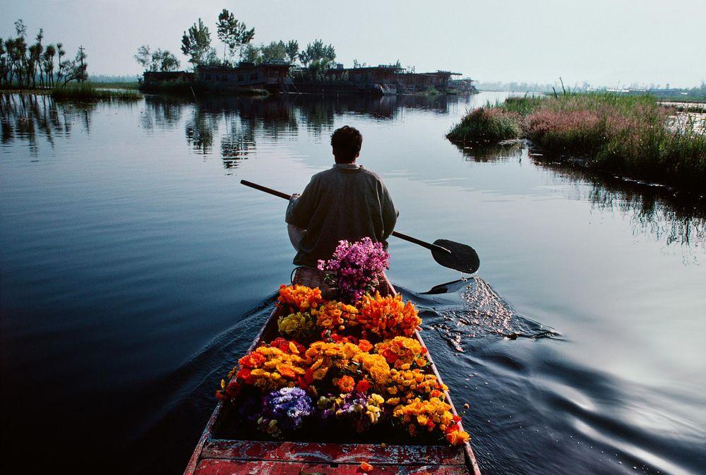 мужчина в лодке с цветами