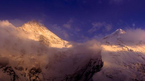 Обои Красивое горное образование с заснеженными вершинами и низкой облачностью