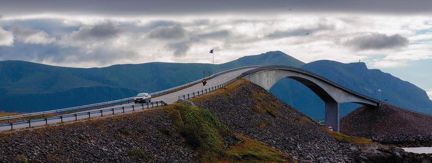 Обои Автомобильный, железобетонный мост, проходящий через неширокую реку невдалеке от горного массива
