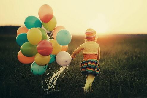 Обои Девочка, держащая в руке связку разноцветных шариков, идущая по полю на фоне солнечных лучей восходящего солнца