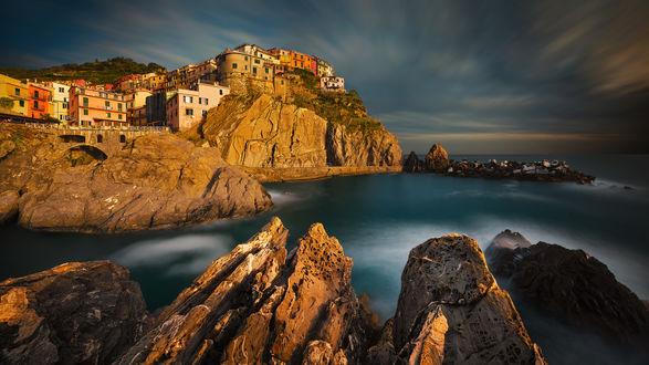 Обои Небольшой рыбацкий городок Лагурия, Италия / Liguria, Italy, стоящий на скалистом морском побережье на фоне вечернего небосклона, автор Pawel Kucharski