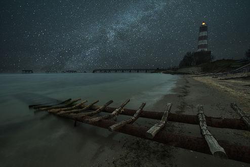 Обои Маяк, стоящий на скалистом, морском побережье на фоне звездного, ночного неба и Млечного пути