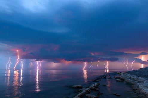 Обои Многочисленные разряды молний на вечернем небосклоне с темными, грозовыми облаками над каменистым морским побережьем