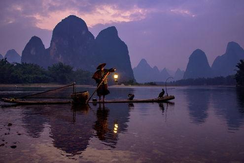 Обои Пожилой китайский рыбак, стоящий на узком, деревянном плоту, держащий в одной руке деревянный шест, а в другой зажженный фонарь, находящийся на мелководье горного озера на рассвете, на носу плота сидит баклан