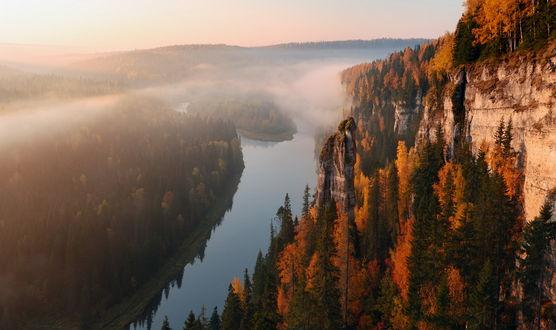 Обои Крутые, отвесные стены скал с растущими на них деревьями с осенней листвой, стоящие на одном из берегов реки, густым хвойным лесом с другой стороны, белыми клочьями тумана, поднимающиеся от водной глади на фоне утреннего небосклона с восходящим солнцем