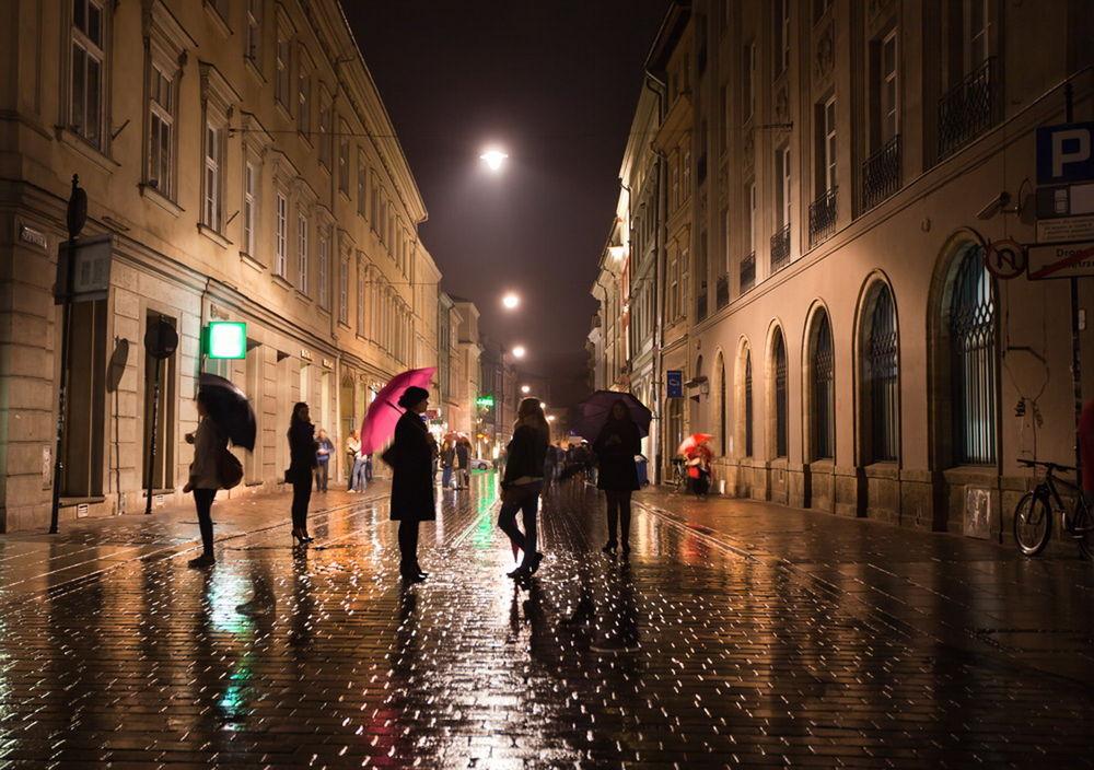 Обои для рабочего стола Люди с зонтикам в руках, прогуливающиеся по ночным, дождливым улицам Кракова, Польша / Krakow, Poland