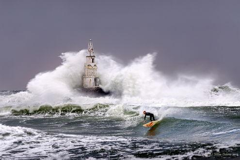 Обои Мужчина-серфингист, катится на океанской волне невдалеке от прибрежного маяка, попавшего под огромную волну