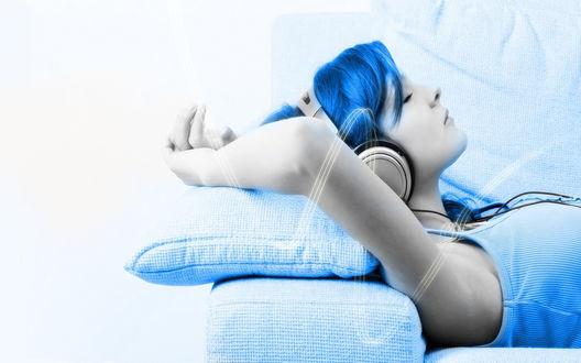 Обои Девушка с голубыми волосами и в наушниках, положила голову затылком на подушку, закинула руки за голову и слушает музыку