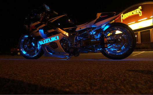 Обои Мотоцикл SUZUKI с синей неоновой посветкой стоит на асфальте, возле здания