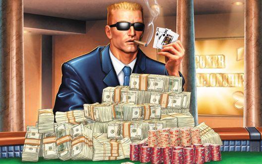 Обои Мужчина игрок в карты с сигарой во рту и темных солнцезащитных очках, сидит за игровым столом казино, заваленным грудой пачек долларов США / USA и фишек, подняв вверх руку с картами