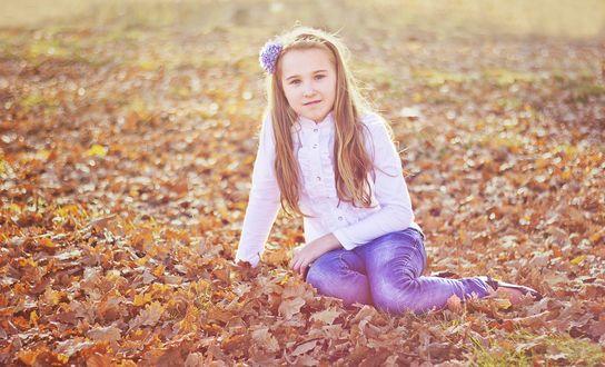 Обои Девочка сидит на осенних листьях